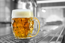 Freshly Poured Draft Lager Beer In A Dimpled Glass Mug On Stainless Steel Counter In A Modern Pub. Black And White Background. Space For Text.