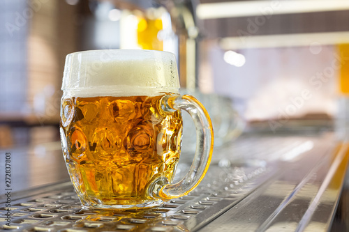Valokuva  Freshly poured draft lager beer in a dimpled glass mug on stainless steel counter in a modern pub