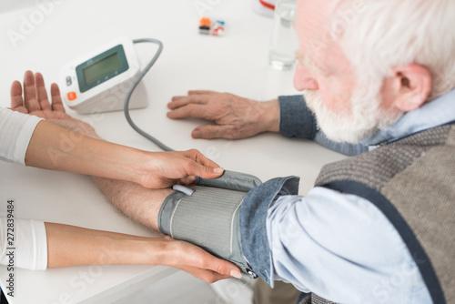 Fotografía  Cropped view of nurse measuring blood pressure of senior man