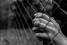 Young Unidentifiable Teenage Boy Holding The Wired Garden  Praying At The Correctional Institute In Black And White, Conceptual Image Of Juvenile Delinquency, Focus On The Boys Hand.