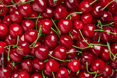 Photo Close up of pile of ripe cherries with stalks and leaves