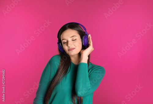 Foto  Attractive young woman enjoying music in headphones on color background