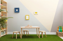 Stylish Playroom Interior With Table, Stools And Green Carpet
