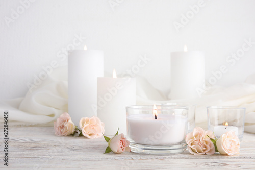 Obraz Composition with burning aromatic candles and roses on wooden table. Space for text - fototapety do salonu