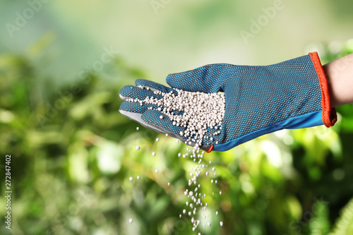 Foto auf Leinwand Texturen Woman in glove pouring fertilizer on blurred background, closeup with space for text. Gardening time