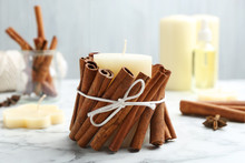 Candle With Cinnamon Sticks On...