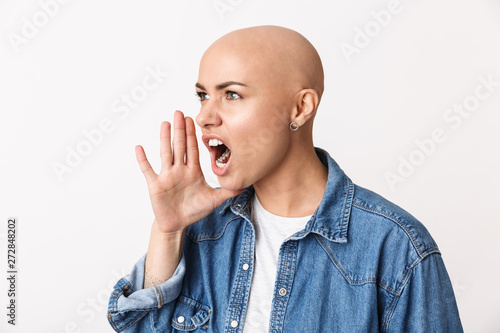 Fotografie, Obraz Beautiful screaming angry bald woman posing isolated over white wall background