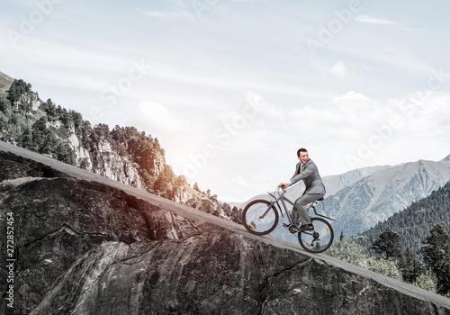 Fotografia Businessman riding downhill by bike