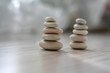 Harmony and balance, two cairns, simple poise pebbles on wooden light white gray background, simplicity rock zen sculpture