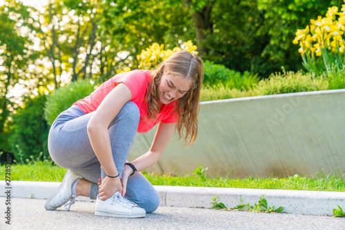 A jogger has injured her ankle while walking and holds it tight Wallpaper Mural