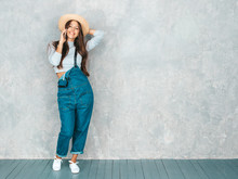 Young Beautiful Woman Speaking On Phone. Trendy Girl In Casual Summer Overalls Clothes And Hat. Funny And Positive Female Posing Near Gray Wall In Studio