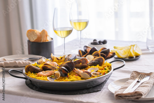 Leinwand Poster Seafood Paella with  prawns, clams, mussels on saffron rice and vegetables and  bottle of white wine on restaurant table