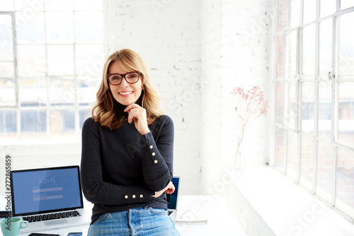 Confident attractive businesswoman relaxing at office desk while looking at camera and smiling