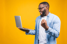 Excited Happy Afro American Man Looking At Laptop Computer Screen And Celebrating The Win Isolated Over Yellow Background.