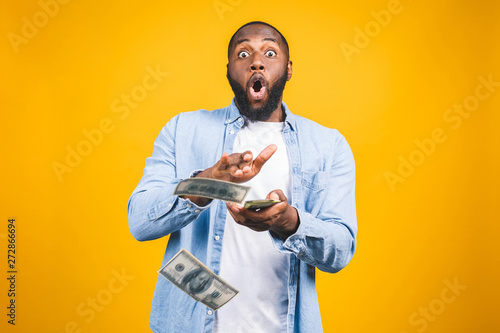 Portrait of a happy young afro american man throwing out money banknotes isolated over yellow background Wallpaper Mural