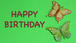Leinwanddruck Bild - two colorful butterflies laying flat on a green background with happy birthday in brown text