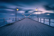 Illuminated wooden pier in Gdynia Orlowo. Early morning on the Baltic Sea. Poland, Europe.