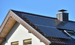 Leinwandbild Motiv Solar panels installed on the roof of a house with tiles in Europe against the background of a blue sky. Green technology