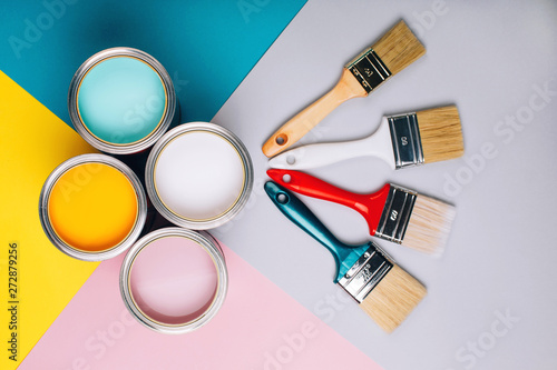 Fotografie, Obraz  Four open cans of paint with brushes on bright background