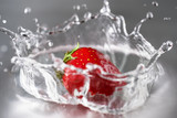 juicy strawberries falling in molovoda with spray
