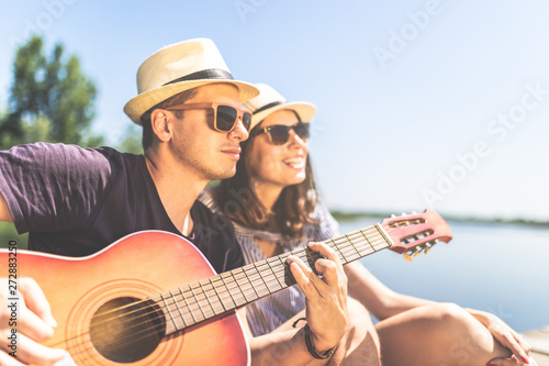 Young couple playing acoustic guitar and singing their favorite song in nature. Love and music concepts. - 272883250