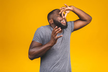 Afro American Man Isolated Against Yellow Background Smelling Something Stinky And Disgusting, Intolerable Smell, Holding Breath With Fingers On Nose. Bad Smells Concept.