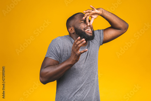 Obraz Afro american man isolated against yellow background smelling something stinky and disgusting, intolerable smell, holding breath with fingers on nose. Bad smells concept. - fototapety do salonu