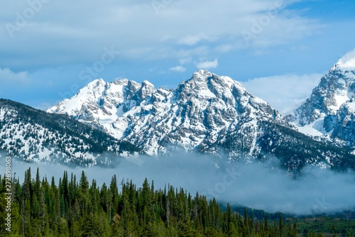 Snow-covered mountain peaks with rolling line of evergreens and mist in foreground