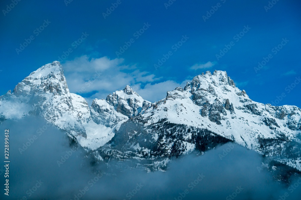 Obraz Snow-covered rocky mountain peaks surrounded by misty clouds  fototapeta, plakat