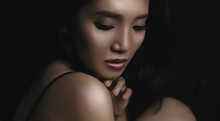 Beautiful Young Woman Closeup Face And Glossy Skin Under Glamour Low Key Concept