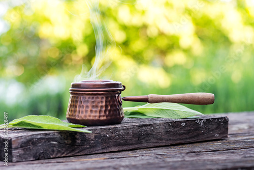 Burning incense and sage on a rustic wooden board in the summer garden