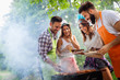 canvas print picture - Friends making barbecue and having lunch in the nature