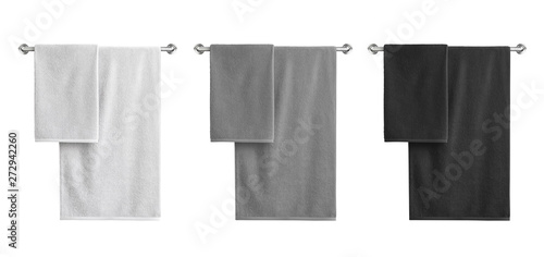White, black and grey cotton terry towels hanging on a rail isolated Fototapete