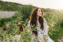 Beautiful Carefree Long Hair Asian Girl In White Clothes On River Side In Grass At Sunset. Sensitivity To Nature Concept