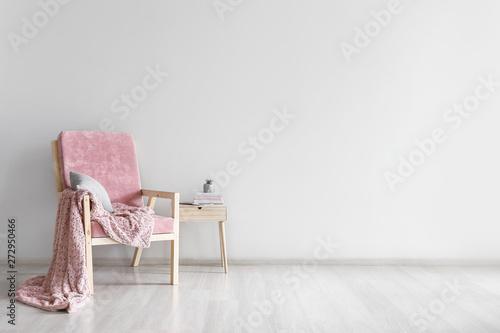Armchair and table near light wall