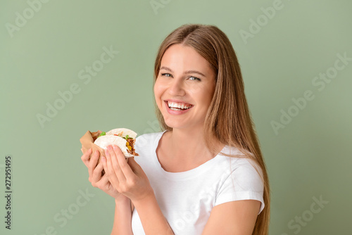 Fototapeta Woman eating tasty taco on color background obraz