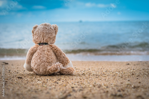Obraz Teddy bear sit alone at the seashore - fototapety do salonu