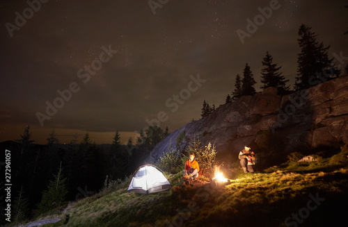 Fototapeta Night camping in the mountains. Young couple hikers having a rest together, sitting beside campfire and illuminated tourist tent. On background big boulder, forest and beautiful night starry sky. obraz na płótnie
