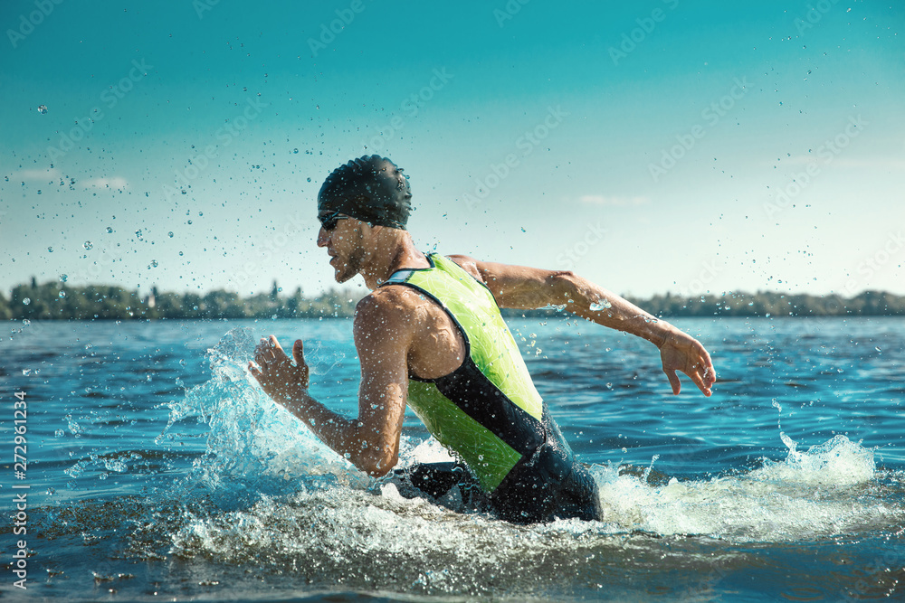Fototapety, obrazy: Professional triathlete swimming in river's open water. Man wearing swim equipment practicing triathlon on the beach in summer's day. Concept of healthy lifestyle, sport, action, motion and movement.