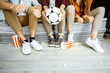 canvas print picture - Friends watching football match. View on their legs with pop cornes and ball on the floor