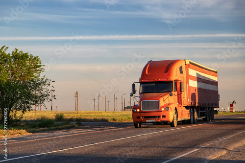A large red truck transports goods on a long-distance road Canvas