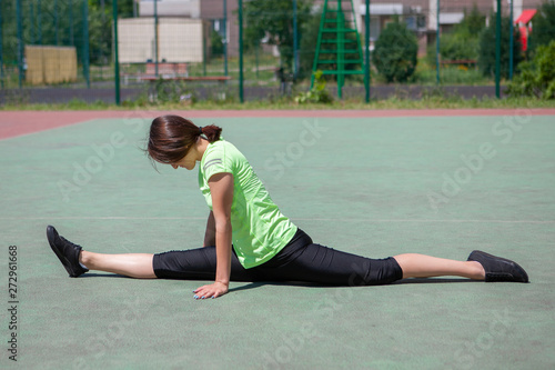 Young fitness girl with a sports figure doing stretching Wallpaper Mural