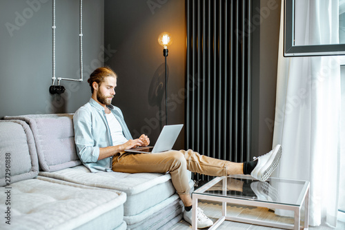 Man working with laptop while sitting on the couch in the living room at home - 272961888