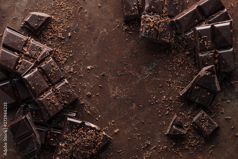 Fototapety, obrazy: Top view of pieces of chocolate bar with chocolate chips on rust metal background