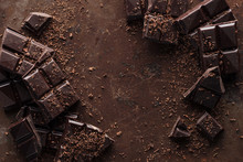 Top View Of Pieces Of Chocolate Bar With Chocolate Chips On Rust Metal Background