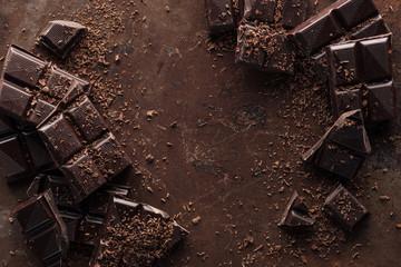 Pogled odozgo na komade čokoladne pločice s čipsom na metalnoj pozadini hrđe
