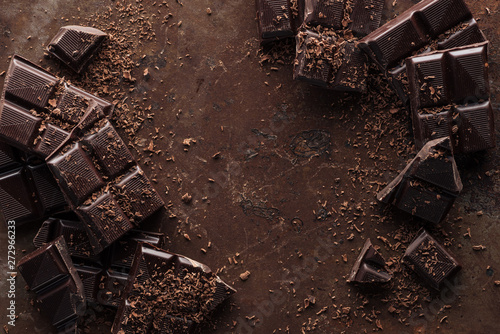 Spoed Foto op Canvas Chocolade Top view of pieces of chocolate bar with chocolate chips on rust metal background