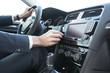 Business Mann bedient Autoradio in Mittelkonsole von Mittelklasse-PKW