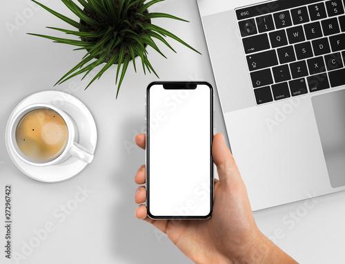 Foto  Smartphone frameless in hand blank screen on business desk - laptop, coffee, gra