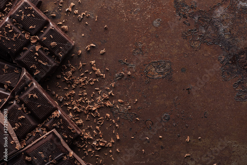 Canvastavla Pieces of chocolate bar with chocolate chips on metal background